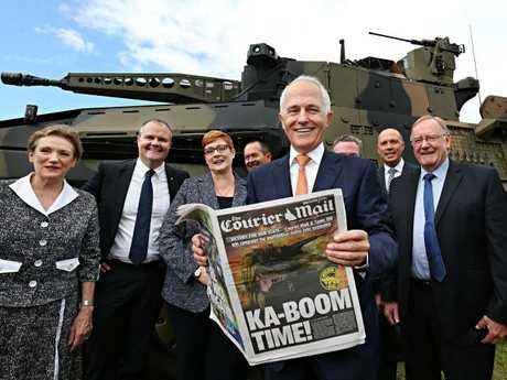 Prime Minister Malcolm Turnbull brandishes yesterday's Courier-Mail at Enoggera Barracks, flanked by Defence Minister Marise Payne and Queensland federal Liberal National MPs. Picture: Annette Dew