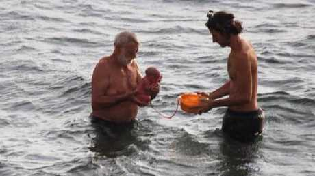 A husband and doctor hold a baby after it was delivered in the sea. Picture: Hadia Hosny El Said/CEN/australscope