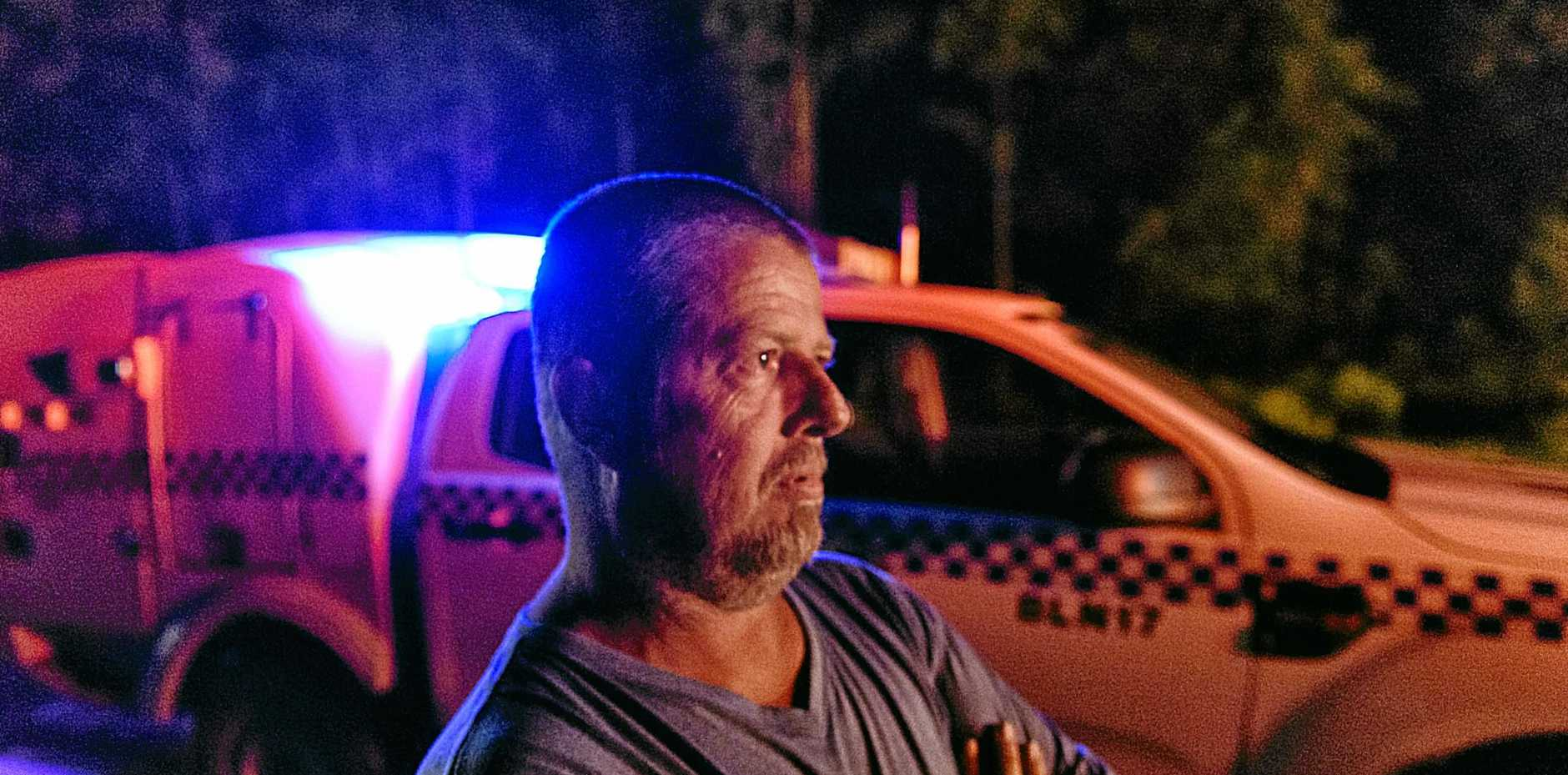 Gladstone truck driver Paul Warren is lit by the lights of emergency service vehicles at the scene of a three car-collision that involved his B-double at Tabbimobile on the Pacific Highway.