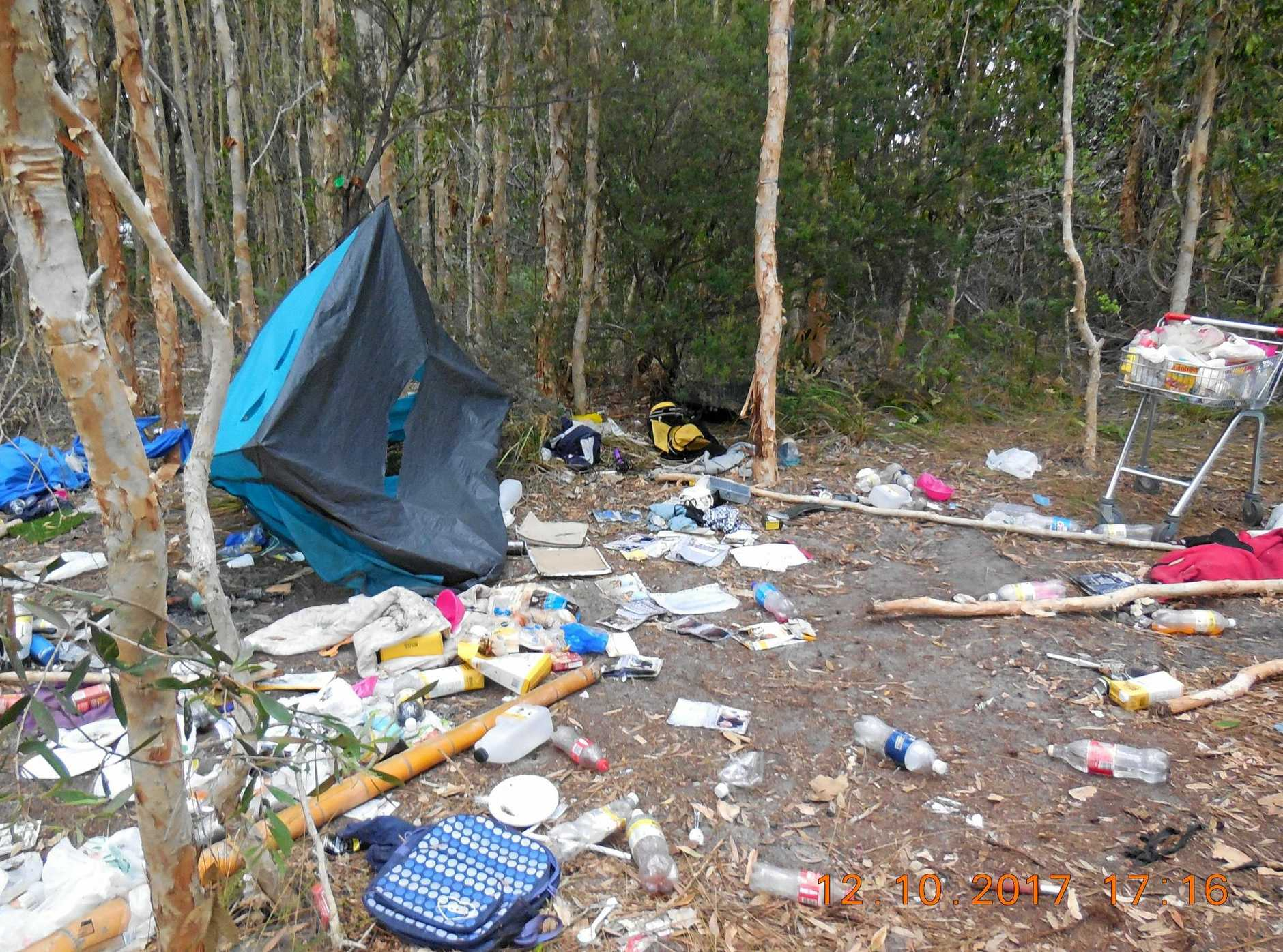 WHAT A WASTE: Tents, food and a shopping trolley were among the litter left scattered around the remains of an illegal camp on the Tin Can Bay foreshore.