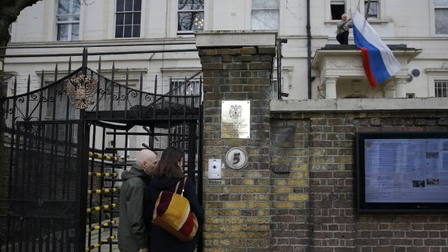 A man untangles a flag at London's Russian Embassy after Britain announced it will expel 23 diplomats over the attack on a former spy. Picture: Alastair Grant