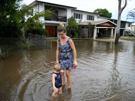 Belinda Strong and her 2-year-old daughter Alicia are seen outside their flood-affected house in Ingham in North Queensland. (AAP Image/Dan Peled)