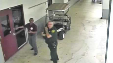 The security video shows deputy Scot Peterson (right) outside Marjory Stoneman Douglas High School a reports come in of a gunman entering the school. Picture: Broward County Sheriff's Office/AP