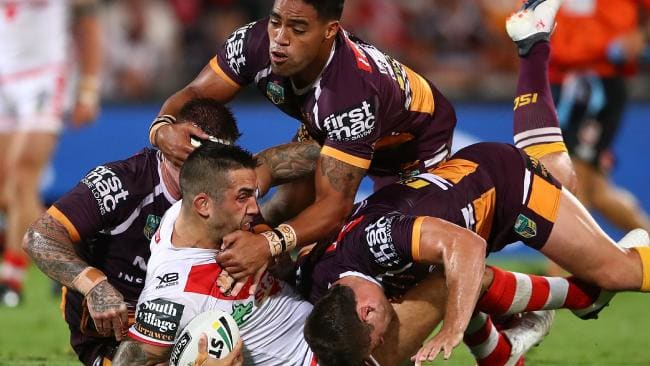 Broncos forwards wrestle Paul Vaughan to the ground in round one. Photo: Mark Kolbe