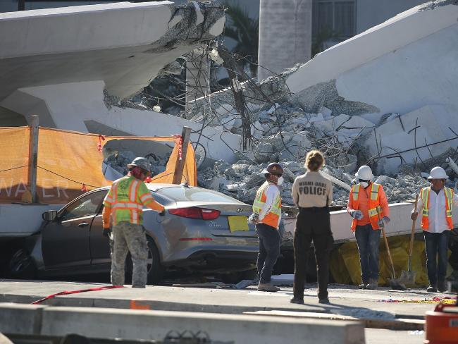 Workers, law enforcement and members of the National Transportation Safety Board investigate the scene where a pedestrian bridge collapsed a few days after it was built over southwest 8th street allowing people to bypass the busy street to reach Florida International University in Miami.  Picture:  Getty