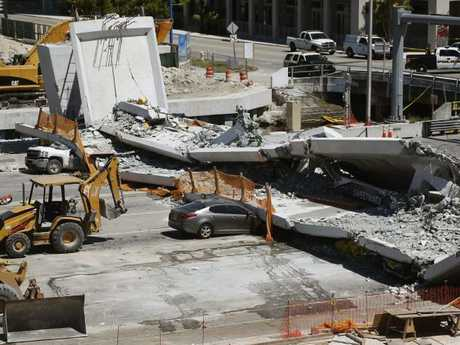 Crushed cars lie under a section of a collapsed pedestrian bridge near Florida International University in the Miami area.  Picture:  AP