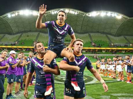 Billy Slater is chaired off by teammates Cameron Smith and Ryan Hoffman.