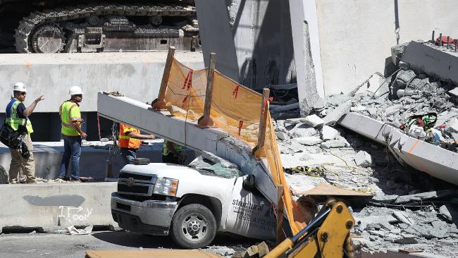 Members of the National Transportation Safety Board investigate the scene where a pedestrian bridge collapsed in Miami, Florida. Picture: Getty