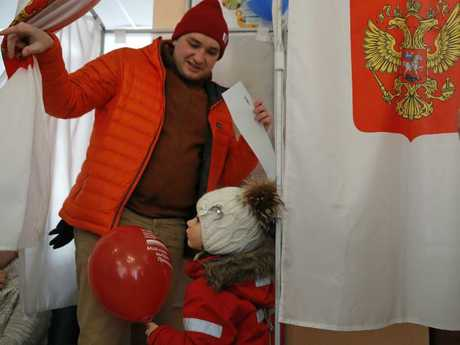 A man and his child leave a polling booth after voting in the Russian election. Picture: AP/Pavel Golovkin