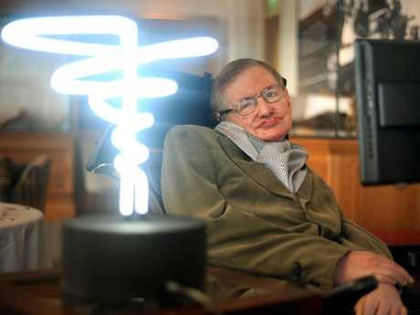 Professor Stephen Hawking poses beside a lamp titled 'black hole light' by inventor Mark Champkins, presented to him during his visit to the Science Museum in London. Picture: AP