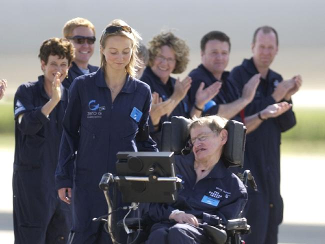 Astrophysicist Stephen Hawking is assisted off the tarmac at the Kennedy Space Center by his caregiver, Monica Guy, as he is applauded by members of the flight crew after completing a zero-gravity flight. Picture: AP