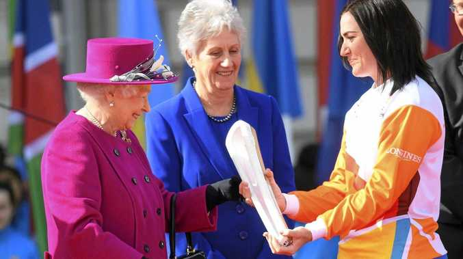 Central Queensland Olympian Anna Meares (right) receives the Commonwealth Games relay baton from Queen Elizabeth II at the launch of the relay at Buckingham Palace on March 13.