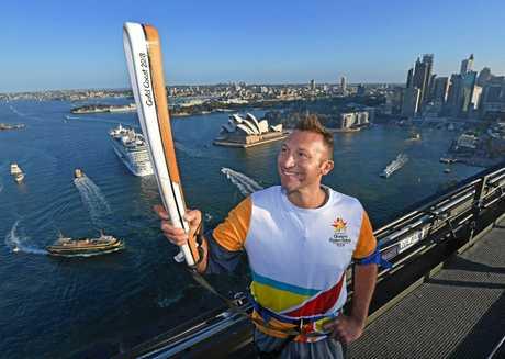 Ian Thorpe with the Queen's Baton Relay atop Sydney Harbour Bridge.