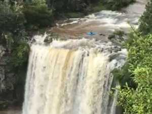 Kayaker plunges over flooded waterfall