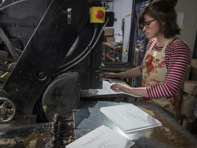 Lottie Small working the press of the royal wedding invites. Picture: Victoria Jones/Pool via AP.