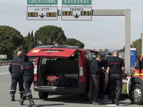 French police and firefighters secure the entrance of Trebes, southern France. Picture: AP Photo/Jean-Paul Bonincontro.