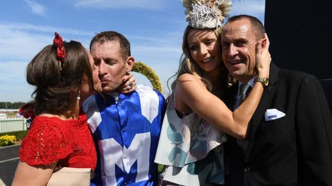 Jockey Hugh Bowman is kissed by wife Christine while trainer Chris Waller is cuddled by wife Stephanie as they celebrate after Winx won.