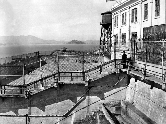 A guard watches inmates play softball at Alcatraz Prison in 1956.