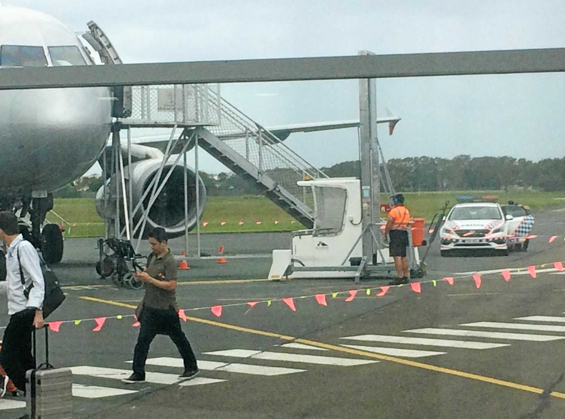 A man was escorted off a plane at the Sunshine Coast Airport by police, after he suffered a mental health episode during the flight. Meanwhile travellers (left) walk to the airport terminal.