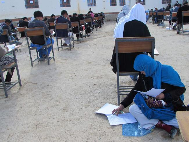 Afghan student Jahantab Ahmadi takes an entrance exam as her baby lies in her lap at Nasir Khusraw private university, in the central city of Nili. Picture: AFP PHOTO/ Yahya Erfan