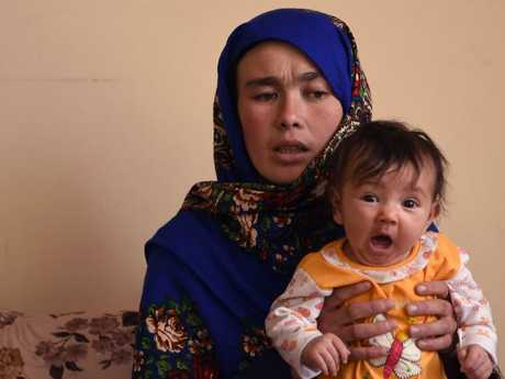 Jahantab Ahmadi, 25, holds her youngest child Khizran, the child she was cradling in an image that has gone viral. Picture: AFP