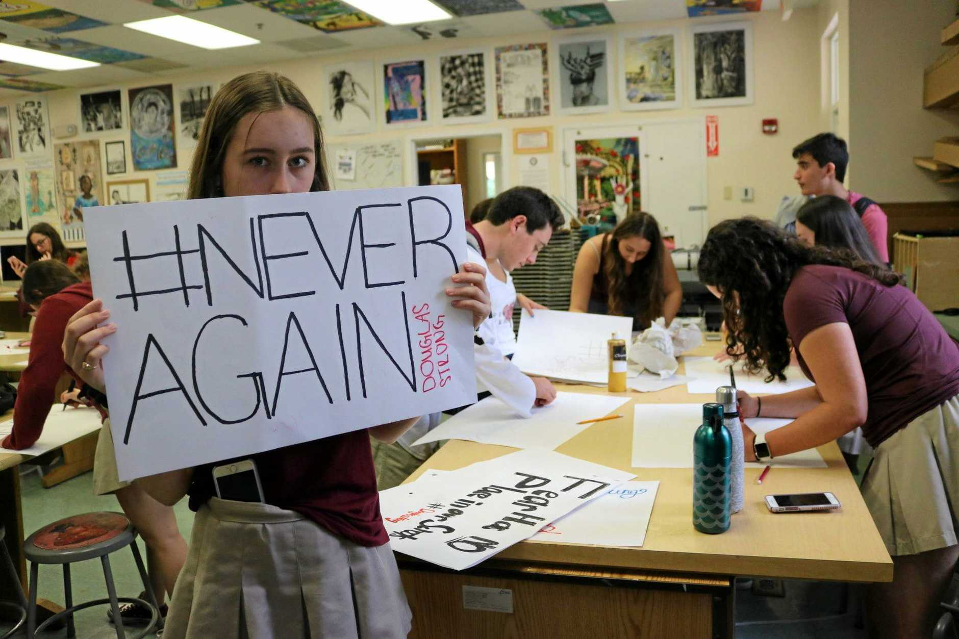 A student holds a sign reading