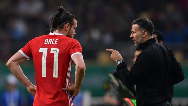 Wales' head coach Ryan Giggs (R) talks with Wales' Gareth Bale during their China Cup International Football Championship final match against Uruguay