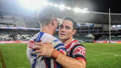 Cooper Cronk embraces his predecessor at the Roosters, the Knights' Mitchell Pearce, left. Picture: AAP
