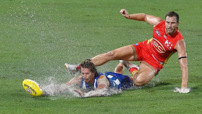 Jed Anderson (left) of the Kangaroos is tackled by Sam Day of the Suns during the round one AFL match between the Gold Coast Suns and the North Melbourne Kangaroos at Cazaly's Stadium. Picture: Ian Hitchcock, Getty Images.