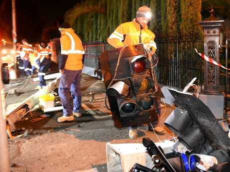 Workers clean up the scene where a tram derailed and crashed. Picture: Nicole Garmston