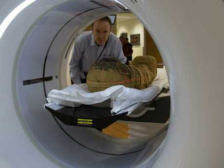Professor John Magnussen places the mummy of the boy Horus into the CT scanner at Macquarie Medical Imaging. Picture: Nicholson Museum.