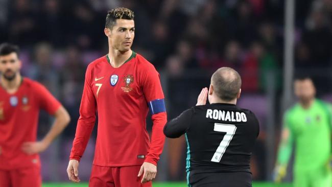 A fan of Portugal's forward Cristiano Ronaldo walks onto the pitch