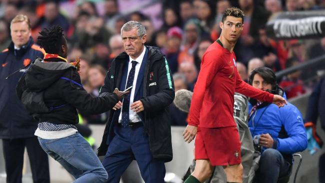 A fan runs next to Portugal's coach Fernando Santos (C) and Portugal's forward Cristiano Ronaldo
