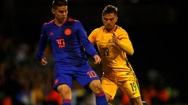 The Socceroos' Josh Risdon tries to keep Columbia's James Rodriguez under wraps.