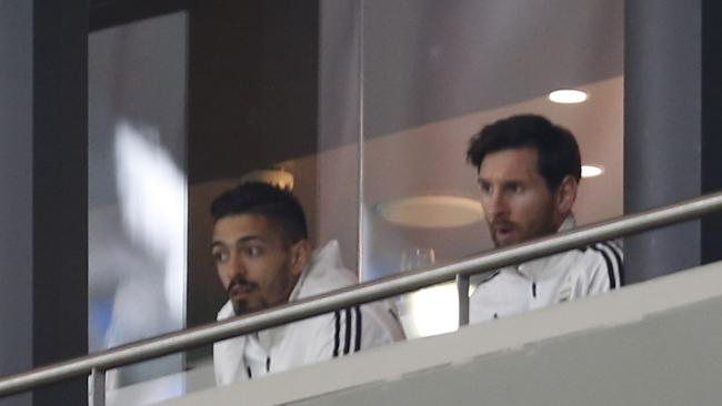 Lionel Messi, right, watches the international friendly soccer match between Spain and Argentina