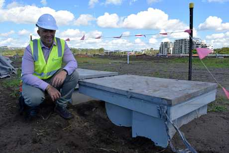 SunCentral development manager Simon Kay inspects underground waste system intake point which will eventually have bins attached to it.