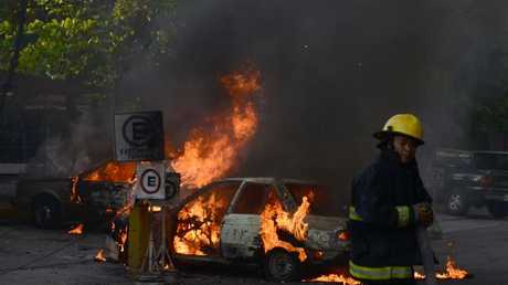 Firefighters extinguish the flames in three vehicles during a wave of violence in Acapulco. Picture: Francisco Robles/AFP