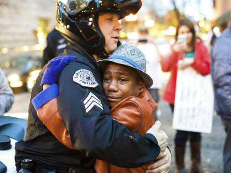 Sgt. Bret Barnum, left, and Devonte Hart, then 12, hug at a rally in Portland where people had gathered in support of the protests in Ferguson. Hart is one of the three other children still missing after a vehicle fell off a cliff. Picture: Johnny Huu