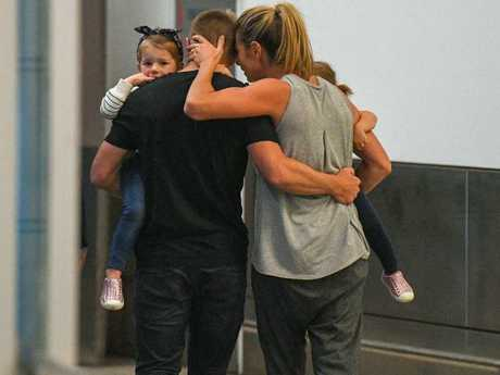Candice guides her husband and their children past the media pack after their arrival at Sydney International Airport. Picture: Brendan Esposito/AAP