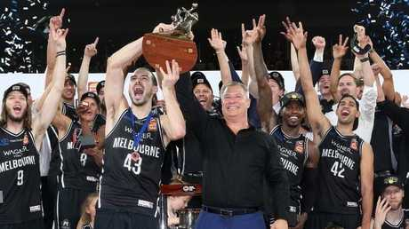 Melbourne United star Chris Goulding and coach Dean Vickerman hold the NBL trophy aloft as the team celebrate their grand final win on Saturday night.