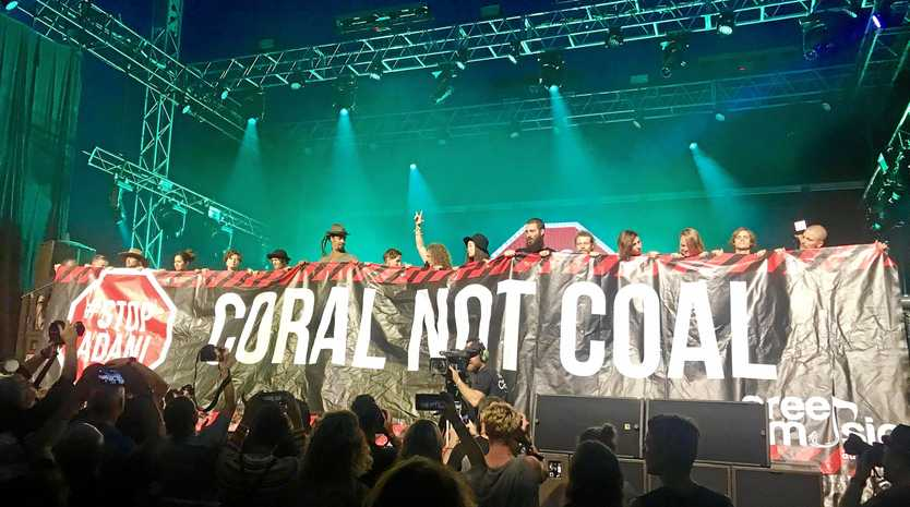BLUESFEST: ARTISTS and activists display a banner against the Adani Charmicael coal mine project for Central Queensland during John Butler trio's performance.