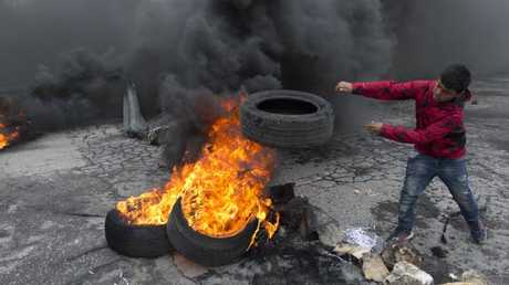 A Palestinian boy burns tyres during the clashes. Picture: AP Photo/Nasser Nasser