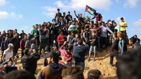 Palestinian protesters wave their national flag during a demonstration commemorating Land Day, near the border with Israel, east of Gaza City, on March 30, 2018. Picture: AFP/Mahmud Hams