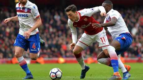 Arsenal's German midfielder Mesut Ozil (C) is fouled by Stoke City's Senegalese defender Badou Ndiaye (R)