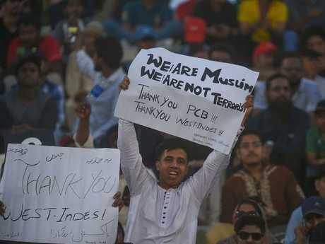 A Pakistani cricket fan holds a sign. AFP PHOTO / RIZWAN TABASSUM