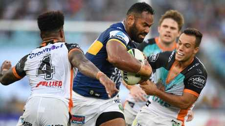 Tony Williams (centre) for the Eels is tackled by Luke Brooks.
