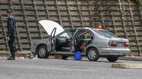 An Explosive Ordnance Response Team searches a car at Redbank Plaza carpark after suspicious items were found, west of Brisbane. Picture: Glenn Hunt/AAP