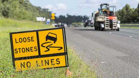 A 'Loose Stones' warning sign at roadworks on the Centenary Highway, Springfield, IMAGE: AAP/Richard Walker
