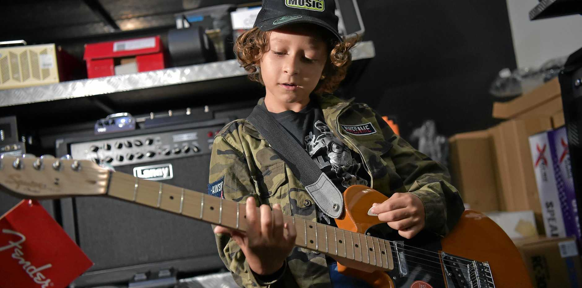 Raiden Macintyre, 10, was able to purchase a new Fender guitar from Shake It Up Music after busking his way to $630 at the Byron Bluesfest.