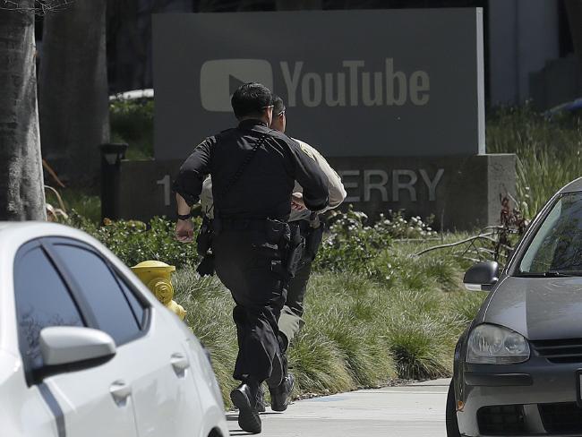 Officers run toward the YouTube office in San Bruno, California. Picture: Jeff Chiu/AP